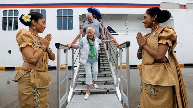 Tourists are welcomed by two Sri Lankan girls as they disembark from MS Europa 2 cruise ship at the main port in Colombo, Sri Lanka on June 7, 2019. (Photo by Dinuka Liyanawatte/Reuters)