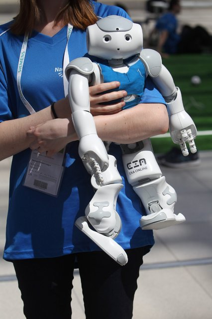 A participant of the 20th RoboCup carries a robot that can play soccer in a hall on the fairgrounds in Leipzig, Germany, June 29, 2016. (Photo by Sebastian Willnow/EPA)