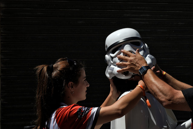 A person is helped put on a Star Wars stormtrooper costume before the start of the parade during the Metropoli (Media Culture and Entertainment Festival) in Gijon, northern Spain, July 3, 2016. (Photo by Eloy Alonso/Reuters)