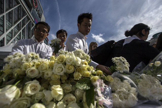 People place flowers for victims killed in Monday's bomb blast during a religious ceremony near at the Erawan shrine, the site of Monday's deadly blast, in central Bangkok, Thailand, August 21, 2015. (Photo by Athit Perawongmetha/Reuters)
