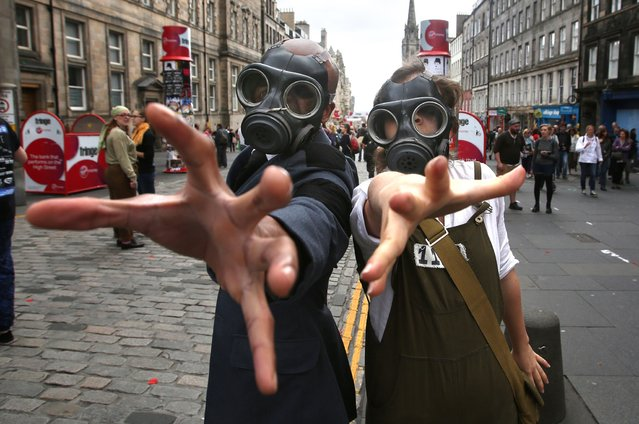 Actors in gas masks pose on the Royal Mile as part of Edinburgh Fringe 2014. (Photo by David Cheskin/PA Wire)