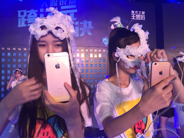 """Women hold mobile phones for a live broadcast as they participate in a reality television show, during which people compete with """"Mark"""", an intelligent software that is able to recognize a human's face, in Hangzhou, Zhejiang Province, China June 30, 2016. (Photo by Xihao Jiang/Reuters)"""