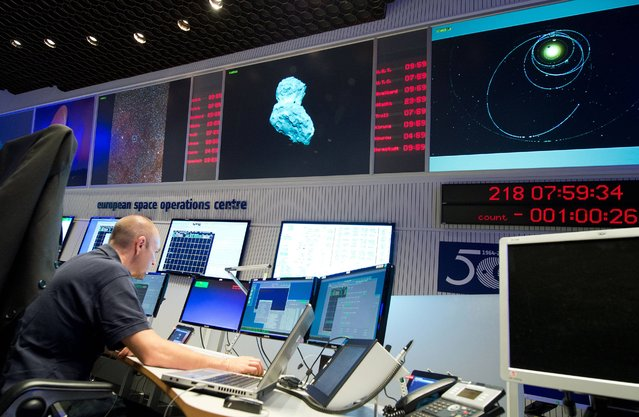 An expert watches his screens at the control center of the European Space Agency, ESA, in Darmstadt, Germany, Wednesday, August 6, 2014. A mission to land the first space probe on a comet reaches a major milestone when the unmanned Rosetta spacecraft finally catches up with its quarry on Wednesday. (Photo by Boris Roessler/AP Photo/DPA)