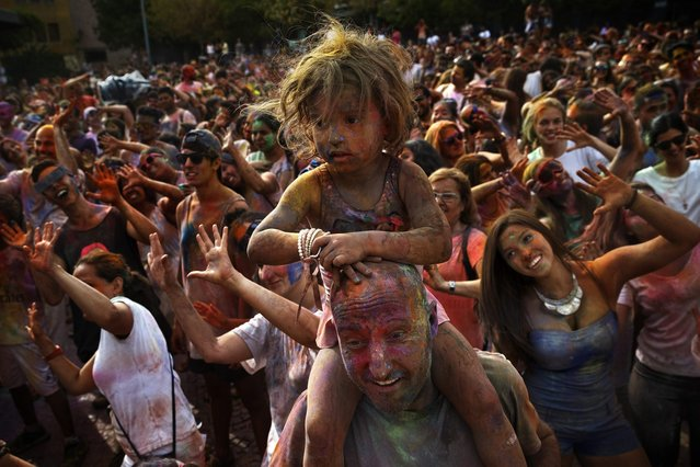 Revelers of the Holi Festival of Colors dance after throwing colored powders in the air in Madrid, Spain, Saturday, August 9, 2014. The festival is fashioned after the Hindu spring festival Holi, which is mainly celebrated in the north and east areas of India. (Photo by Daniel Ochoa de Olza/AP Photo)