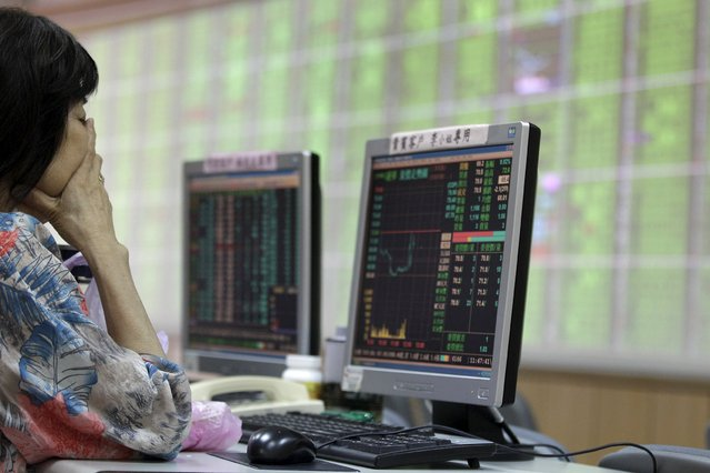 A woman monitors stock market prices inside a brokerage in New Taipei city, Taiwan, August 24, 2015. Taiwan stocks sank by more than 6 percent on Monday morning, following bruising losses in U.S. and regional bourses. (Photo by Pichi Chuang/Reuters)