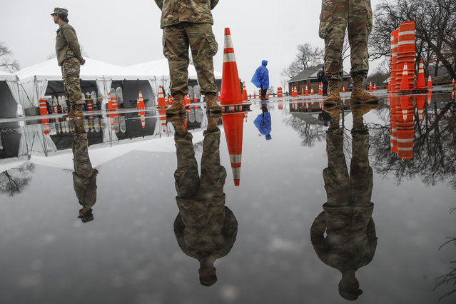 """National Guard personnel stand at attention as they wait for patients to arrive for COVID-19 coronavirus testing facility at Glen Island Park, Friday, March 13, 2020, in New Rochelle, N.Y.  State officials have set up a """"containment area"""" in the New York City suburb, where schools and houses of worship are closed within a 1-mile radius of a point near a synagogue where an infected person with coronavirus had attended events. State officials stress it is not a lockdown. The vast majority of people recover from the new coronavirus. According to the World  Health Organization, most people recover in about two to six weeks, depending on the severity of the illness. (Photo by John Minchillo/AP Photo)"""