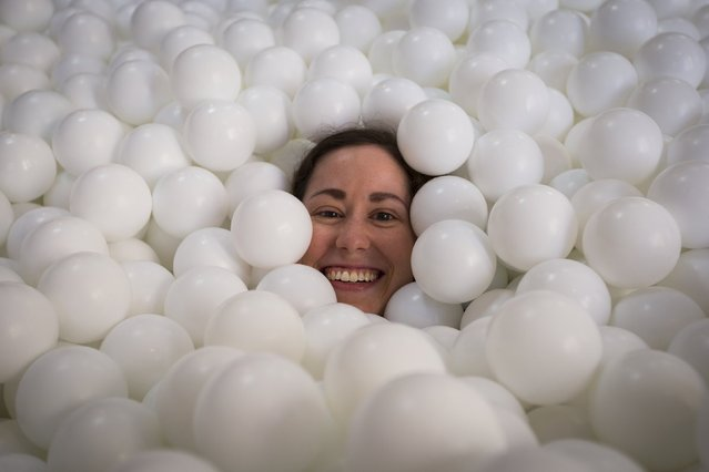 "A woman smiles as she is buried under white balls in the ""JumpIn!"" ball pit, an interactive art installation by creative agency Pearlfisher made up of 81,000 white balls, in New York City August 25, 2015. (Photo by Mike Segar/Reuters)"