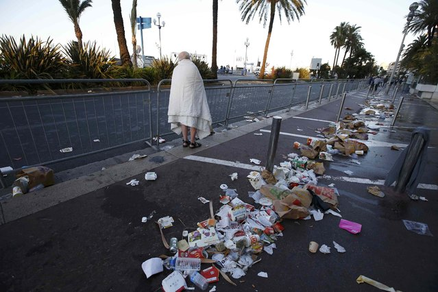 A man walks through debris scatterd on the street the day after a truck ran into a crowd at high speed killing scores celebrating the Bastille Day July 14 national holiday on the Promenade des Anglais in Nice, France, July 15, 2016. (Photo by Eric Gaillard/Reuters)