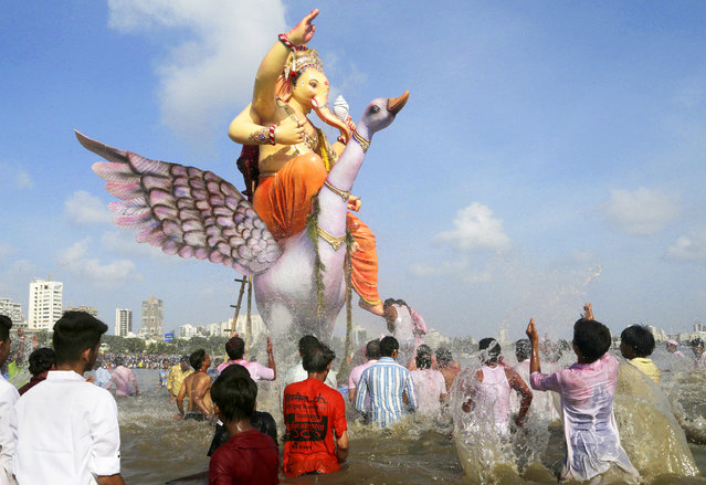 Hindu devotees stand around a giant idol of the elephant-headed god Ganesha before it is immersed in the Arabian Sea on the final day of the ten-day long Ganesh Chaturthi festival in Mumbai, India, Tuesday, September 5, 2017. (Photo by Rajanish Kakade/AP Photo)