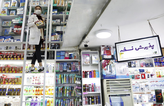 A pharmacist works in a drugstore in downtown Tehran, Iran, Tuesday, February 25, 2020. The head of Iran's counter-coronavirus task force has tested positive for the virus himself, authorities announced Tuesday, showing the challenges facing the Islamic Republic amid concerns the outbreak may be far wider than officially acknowledged. The announcement comes as countries across the Mideast say they've had confirmed cases of the virus that link back to Iran, which for days denied having the virus. (Photo by Ebrahim Noroozi/AP Photo)
