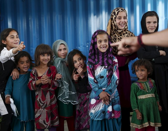 Internally displaced children watch as a member of Afghan Mobile Mini Circus for Children (MMCC) performs at a camp in Kabul, Afghanistan August 13, 2015. (Photo by Ahmad Masood/Reuters)