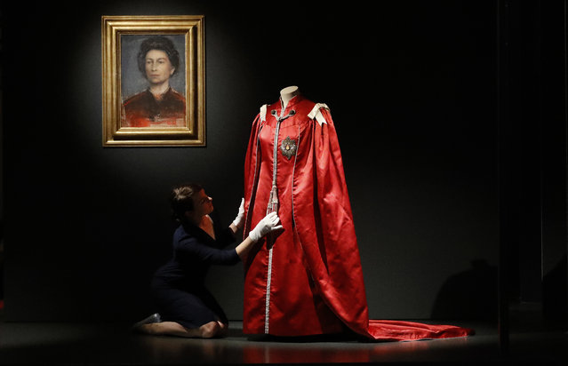 A woman adjusts the Mantle of the Order of the British Empire at an exhibition at Buckingham Palace in London, Thursday, July 21, 2016. In celebration of Her Majesty's 90th birthday this year, visitors to the Summer Opening of the State Rooms at Buckingham Palace will enjoy an unprecedented display of The Queen's outfits, from childhood to the present day, in the special exhibition Fashioning a Reign: 90 Years of Style from The Queen's Wardrobe. (Photo by Frank Augstein/AP Photo)