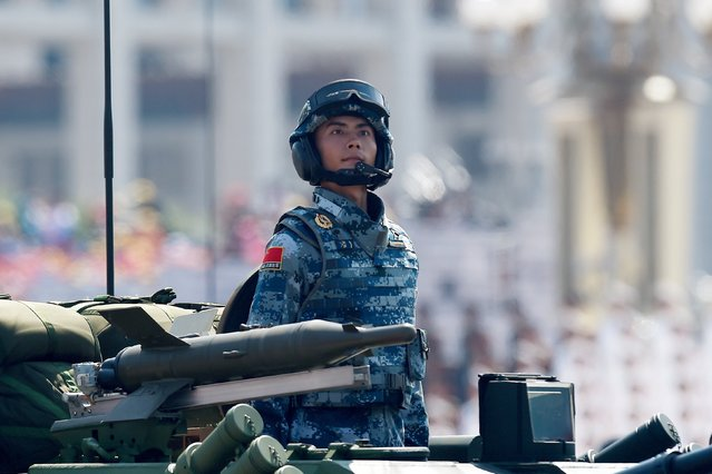 A soldier rides in a Chinese military vehicle as it is paraded through Tiananmen Square in Beijing on September 3, 2015 during a military parade to mark the 70th anniversary of victory over Japan and the end of World War II. (Photo by Wang Zhao/Reuters)