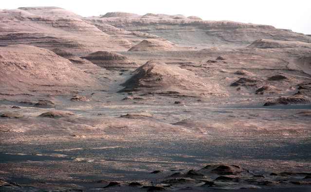 This image is from a test series used to characterize the 100-millimeter Mast Camera on NASA's Curiosity rover. It was taken on August 23, 2012, and looks south-southwest from the rover's landing site. The 100-millimeter Mastcam has three times better resolution than Curiosity's 34-millimeter Mastcam, though it has a narrower field of view. In the distance, there are dark dunes and then the layered rock at the base of Mount Sharp. Some haze obscures the view, but the top ridge, depicted in this image, is 10 miles (16.2 kilometers) away. Scientists enhanced the color in this version to show the Martian scene under the lighting conditions we have on Earth, which helps in analyzing the terrain. (Photo by NASA/JPL-Caltech/MSSS)