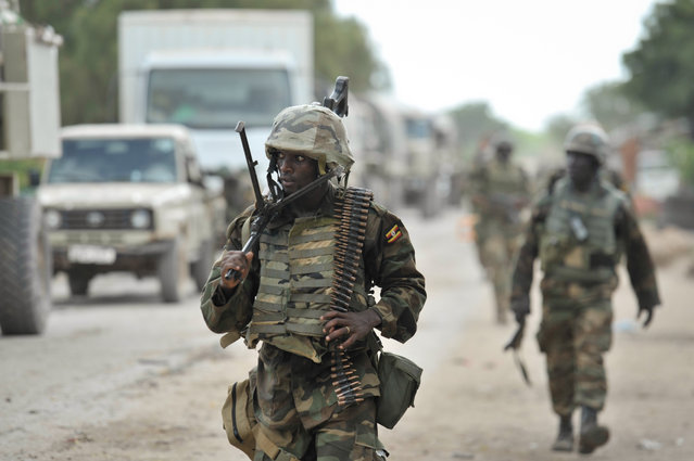 A handout photograph made available by the African Union Mission in Somalia (AMISOM) showing Ugandan troops, as part of the African Union Mission in Somalia, marching through the town of Golweyn after having liberated it from Al Shabab in Somalia's Lower Shabelle region on 30 August 2014. The AMISOM offensive is part of Operation Indian Ocean, which aims to liberate several new towns in the region from the terrorist organization. (Photo by Tobin Jones/EPA/AMISOM)
