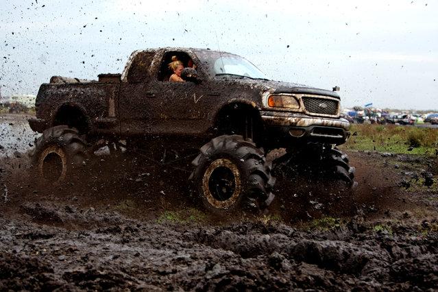 A truck races through the mud bog. (Photo by Gary Coronado/The Palm Beach Post)