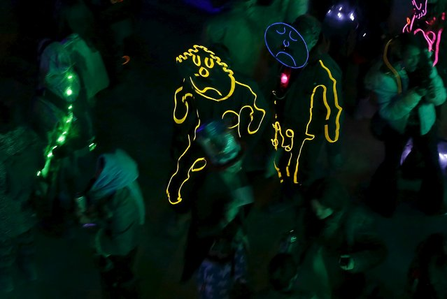 """Participants wear illuminated costumes during the Burning Man 2015 """"Carnival of Mirrors"""" arts and music festival in the Black Rock Desert of Nevada September 5, 2015. (Photo by Jim Urquhart/Reuters)"""