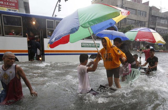 A woman, standing on an improvised cart along a flooded road, reacts to waves caused by a passing bus as tropical storm Fung-Wong battered the Philippine capital Manila September 19, 2014. (Photo by Erik De Castro/Reuters)