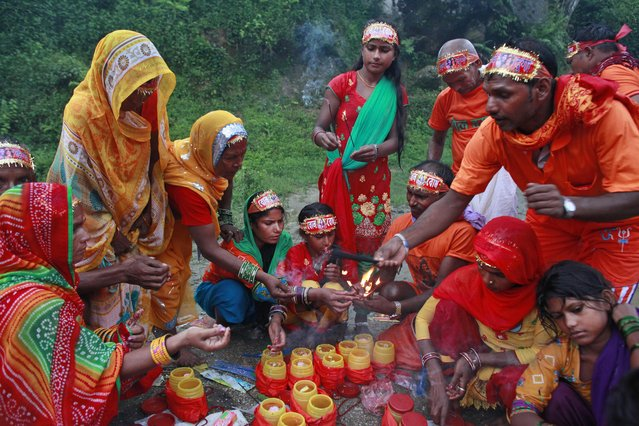 Hindu devotees perform rituals during the Bol Bom pilgrimage, on the outskirts of Kathmandu, Nepal, Monday, August 8, 2016. During this pilgrimage, devotees walk miles barefooted before offering water collected from Bagmati river, at the Pashupatinath temple in Katmandu. Shravan Somwar or Monday of Hindu calendar month of Shravan is considered auspicious for offering prayers to Lord Shiva, the god of destruction. (Photo by Niranjan Shrestha/AP Photo)