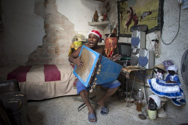 Santeria practitioner Miguel Angel, 36, sings religious songs at his home in downtown Havana, August 28, 2015. (Photo by Alexandre Meneghini/Reuters)