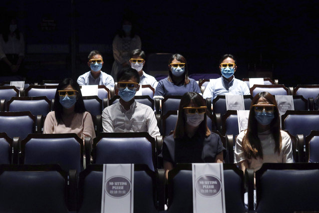 Staff members wearing face masks and 3D glasses as they demonstrate the social distancing in the theatre during a media tour at the Hong Kong's Disneyland on Wednesday, June 17, 2020, a day before the theme park reopen after nearly four months of closure due to the coronavirus pandemic. (Photo by Kin Cheung/AP Photo)