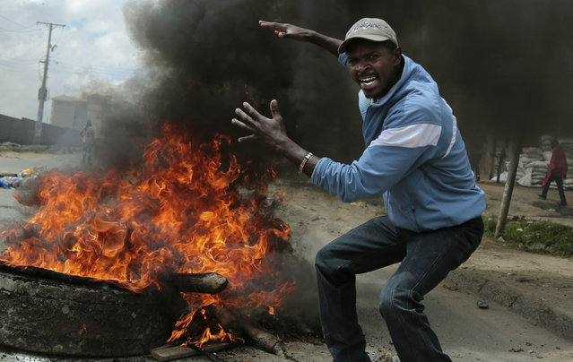 An opposition supporter gestures at a barricade during clashes with police in the Jacaranda grounds quarter in Nairobi, Kenya, Tuesday, November 28, 2017. (Photo by Brian Inganga/AP Photo)