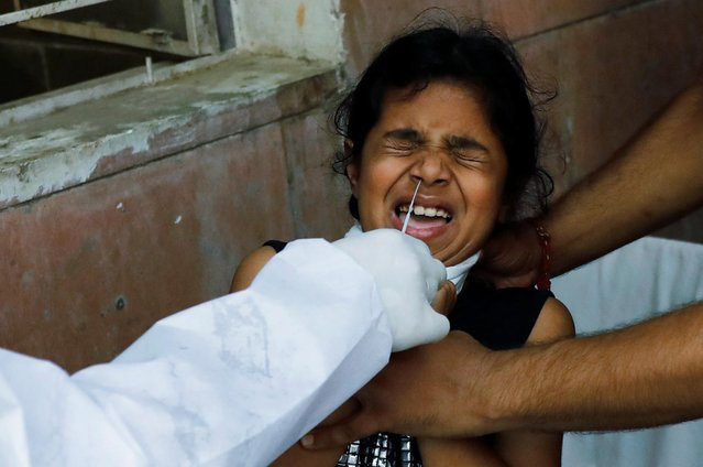 A girl reacts as a medical worker collects a sample from her at a centre to conduct tests for the coronavirus disease (COVID-19), amidst its spread in New Delhi, India June 25, 2020. (Photo by Anushree Fadnavis/Reuters)