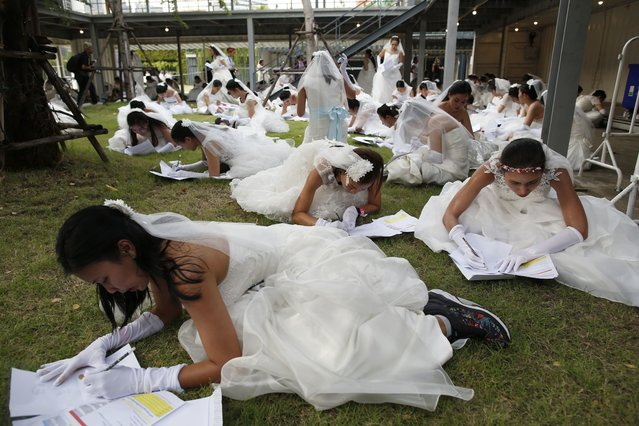 """Thai brides-to-be do the maths task in the """"Running of the Brides"""" event in Bangkok, Thailand, 02 December 2017. (Photo by Rungroj Yongrit/EPA/EFE/Rex Features/Shutterstock)"""