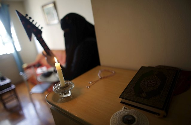Gisele Marie, a Muslim woman and professional heavy metal musician, plays her Gibson Flying V electric guitar next to a Koran at her house in Sao Paulo August 11, 2015. (Photo by Nacho Doce/Reuters)