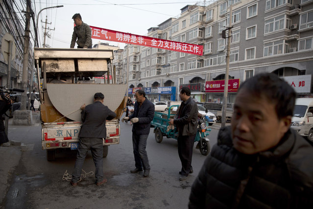 """Workers load kitchen equipment near propaganda slogans at left that read: """"Carry forward righteousness, Differentiate right and wrong, Fully support eviction work"""" onto a truck from a restaurant that's closed by the eviction in the outskirts of Beijing Monday, November 27, 2017. Authorities in Beijing have been evicting domestic migrant workers from the capital in droves, triggering a public outcry over the harsh treatment of people the city depends on to build their skyscrapers, care for their children and take on other lowly-paid work. (Photo by Ng Han Guan/AP Photo)"""