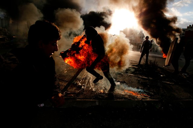 A Palestinian protester runs after catching fire during clashes with Israeli troops at a protest against US President Donald Trump' s decision to recognize Jerusalem as the capital of Israel, near the Jewish settlement of Beit El, near the West Bank city of Ramallah on December 7, 2017. (Photo by Abbas Momani/AFP Photo)