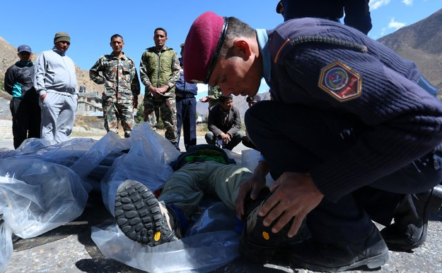 Nepalese police prepare to move the bodies of trekkers killed following a snowstorm and an avalanche onto a plane to be transported to Kathmandu in Jomsom on October 17, 2014. (Photo by Skanda Gautam/AFP Photo)