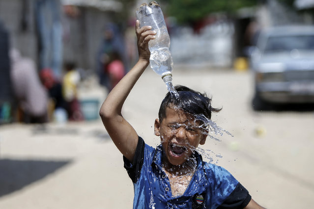 A Palestinian boy pours water over his head in Khan Yunis in the southern Gaza Strip, on July 22, 2020. (Photo by Mohammed Abed/AFP Photo)