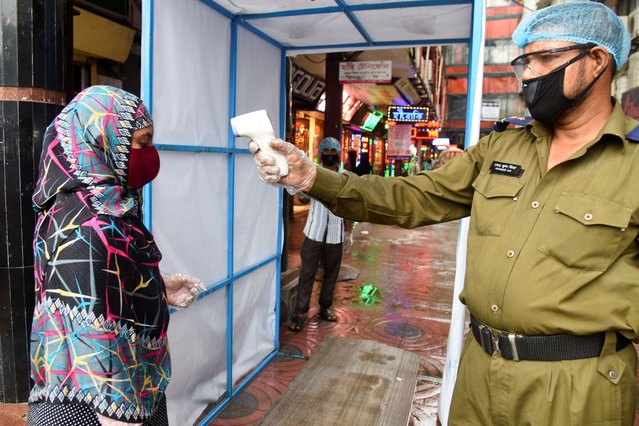 A security personal checks the body temperature of a shopper at the entrance of a shopping mall during the coronavirus outbreak in Dhaka, Bangladesh, on June 28, 2020 (Photo by Mamunur Rashid/NurPhoto via Getty Images)