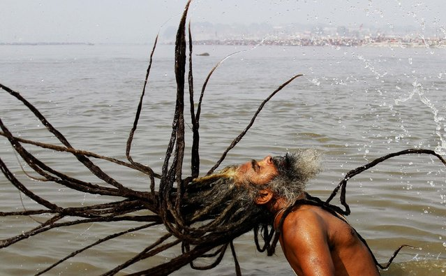 A Sadhu, or a Hindu holy man, takes a dip at Sangam, confluence of the Rivers Ganges, Yamuna and mythical Saraswati, during the annual traditional fair of Magh Mela in Allahabad, India, January 30, 2012. Hundreds of thousands of devout Hindus bathe at the confluence during the astronomically auspicious period of over 45 days celebrated as Magh Mela. (Photo by Rajesh Kumar Singh/AP Photo)