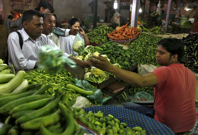 Customers buy vegetables at a market in Ahmedabad, India, September 29, 2015. Indian households expect consumer inflation to remain in double digits over the next three months and the next year, according to a quarterly survey by the central bank on Tuesday, even as recent data showed retail prices have remained muted. (Photo by Amit Dave/Reuters)