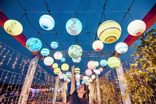 A person touches a colorful light ball at the opening ceremoby of the first Windmill and Light Show Festival in Xingan county, Ji'an city, east China's Jiangxi province, 25 July 2020. (Photo by Imaginechina via AP Images)