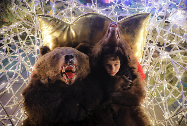 In this Thursday, December 28, 2017, picture children wearing bear fur costumes pose at a Christmas fair, in Piatra Neamt, Romania. (Photo by Vadim Ghirda/AP Photo)