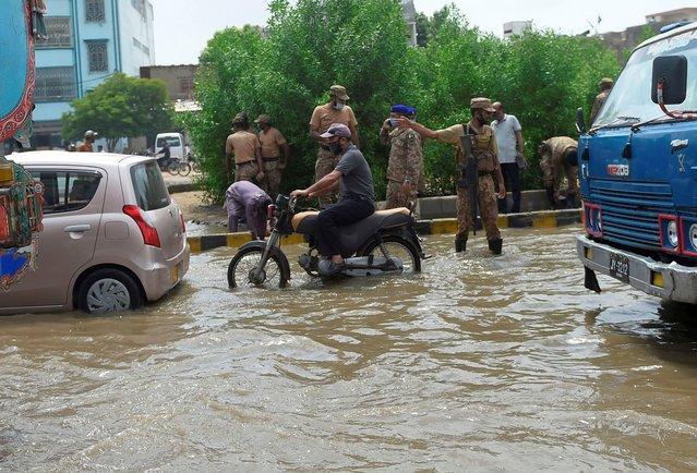 Pakistani army soldiers take part of rescue operation in a flooded area after heavy monsoon rains in the Pakistan's port city of Karachi on August 22, 2020. (Photo by Rizwan Tabassum/AFP Photo)