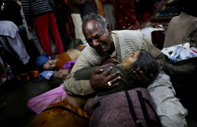 A man weeps as he holds his wife who was killed in a stampede on a railway platform at the main railway station in Allahabad, India, on February 10, 2013. At least ten Hindu pilgrims attending the Kumbh Mela were killed and more then thirty were injured during a stampede on an overcrowded staircase. (Photo by Kevin Frayer/Associated Press)