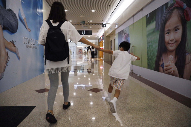 "Pamela Lam plays with her son on the way to school in Hong Kong, Friday, July 3, 2020. Lam's 6-year-old son fell in love with the Hong Kong protest anthem, ""Glory to Hong Kong"", the first time he heard it and sings it quite often. Thanks to a sweeping new national security law, though, singing it in public is now risky. Lam agreed to be photographed only if her face was not shown, fearing possible retribution from authorities. (Photo by Kin Cheung/AP Photo)"