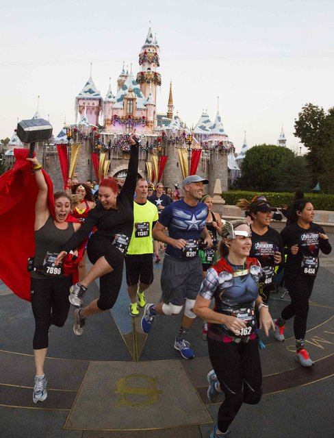 Runners in super hero outfits stream past Sleeping Beauty's Castle during the Avengers Super Heroes Half Marathon in and around the Disney Parks in Anaheim, California November 16, 2014. (Photo by Eugene Garcia/Reuters)