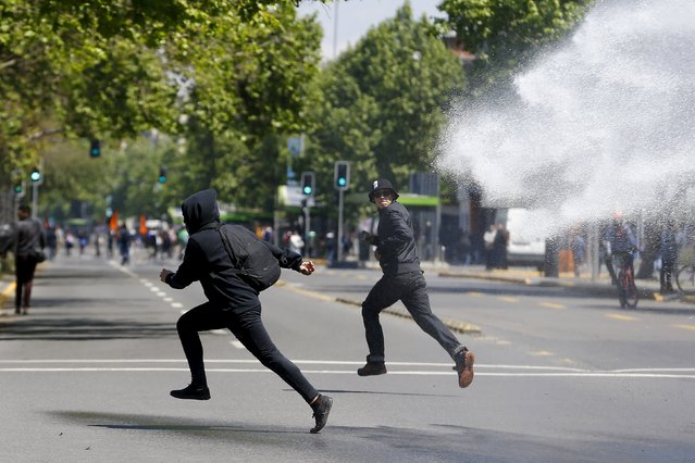 Student protesters run away from a riot police water cannon during a demonstration to demand changes in the education system in Santiago, Chile, October 15, 2015. (Photo by Ivan Alvarado/Reuters)