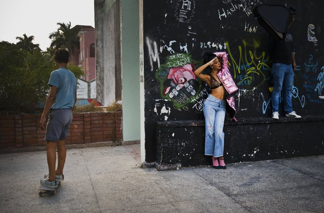 In this January 11, 2018 photo, a young model and a member of the lighting crew use as their backdrop an abandoned gym that was converted into space for skateboarders, the day of the space's inauguration inside the Educational complex Ciudad Libertad, a former military barracks that the late Fidel Castro turned into a school complex after the revolution in Havana, Cuba. Cuba's official sports establishment once took a dim view of skaters, but over the past 15 years it has tolerated, and occasionally encouraged, skateboarding. (Photo by Ramon Espinosa/AP Photo)