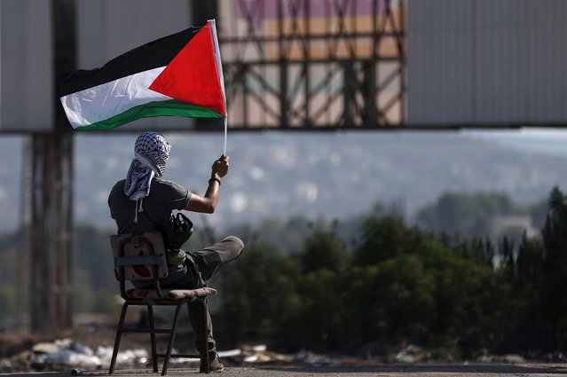 A Palestinian protester waves a Palestinian flag during clashes with Israeli troops at the Israeli Hawara checkpoint near the West Bank city of Nablus October 16, 2015. The unrest that has engulfed Jerusalem and the occupied West Bank, the most serious in years, has claimed the lives of 34 Palestinians and seven Israelis. (Photo by Ahmad Talat/Reuters)