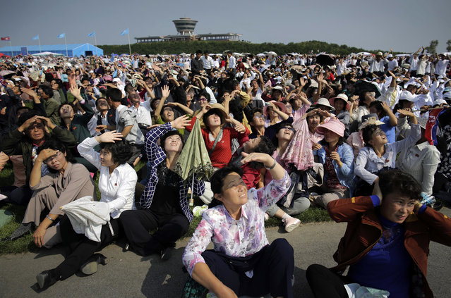 North Koreans shield their eyes from the sun as they watch an aerial display on Saturday, September 24, 2016, in Wonsan, North Korea. North Korea opened an air festival featuring sky diving, air force demonstrations and lots of beer Saturday to promote a newly renovated and upgraded airport in the coastal city of Wonsan, an area where it hopes to draw more foreign tourists. The two-day International Friendship Air Festival has been touted for months by the North as part of its ongoing effort to draw more tourists. The Wonsan area with its beaches and rugged mountain scenery, including a ski resort, is already popular with Chinese tourists and in the past attracted many Japanese, who came by ferry. Japanese visits dropped off abruptly as political relations deteriorated over revelations that North Korea had abducted more than a dozen Japanese people in the 1970s and 80s and then over its nuclear weapons and long-range missile programs. (Photo by Wong Maye-E/AP Photo)