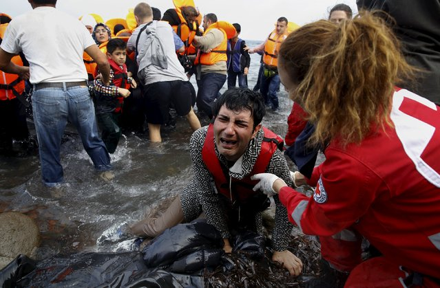 A Greek Red Cross volunteer comforts a crying Syrian refugee moments after disembarking from a flooded raft at a beach on the Greek island of Lesbos after crossing a part of the Aegean Sea from the Turkish coast on an overcrowded raft October 20, 2015. (Photo by Yannis Behrakis/Reuters)