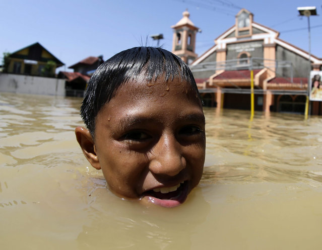 A Filipino boy wades next to a church at the flood-hit town of Calumpit, Bulacan province, northern Manila, Philippines, 21 October 2015. The death toll in a powerful storm that battered the northern Philippines has risen to 35, with nearly half a million people displaced, disaster relief officials said. Most of the fatalities either drowned in floods that reached up to the roofs in some areas, were buried in landslides, or hit by toppled trees or collapsed walls caused by typhoon Koppu. (Photo by Francis R. Malasig/EPA)