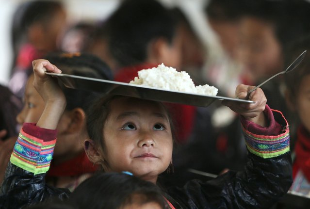 An ethnic Miao minority child wearing traditional costume carries a plate of rice during lunchtime at the village of Basha in Congjiang county, Guizhou province, November 27, 2014. The village, an ethnic Miao settlement with a population of 2,200, is believed to be the last community authorized by the Chinese government to keep guns. (Photo by Sheng Li/Reuters)