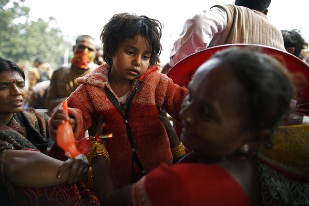 "A girl is united with her mother at the lost and found camp after getting lost in the crowd during the ""Gadhimai Mela"" festival held in Bariyapur November 29, 2014. (Photo by Navesh Chitrakar/Reuters)"